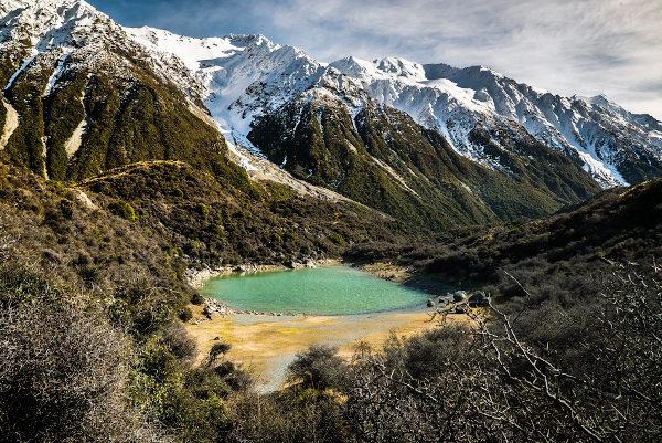 Paisagem natural típica do interior da Nova Zelândia, marcada pela presença de lagos de água doce e de neve no topo das montanhas.