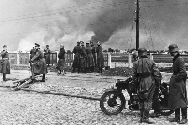 Cidade de Varsóvia em chamas ao fundo depois de ataques dos alemães. A invasão da Polônia foi o estopim da Segunda Guerra Mundial.[1]