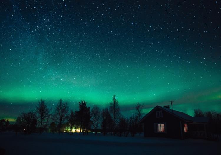 Foto de paisagem com árvores e casa e céu estrelado com aurora boreal.