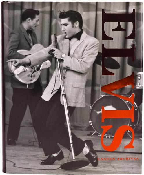 Foto de Elvis Presley cantando e dançando e o guitarrista de sua banda ao fundo.
