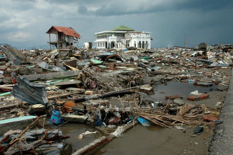 Foto de local da Indonésia devastado após um tsunami; no primeiro plano, rastros da destruição, ao fundo, um edifício.