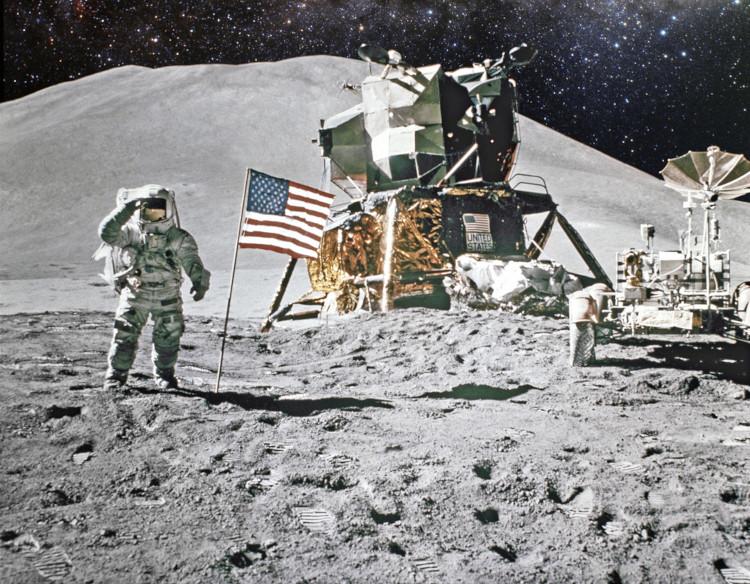 Astronauta em solo lunar ao lado de bandeira estadunidense