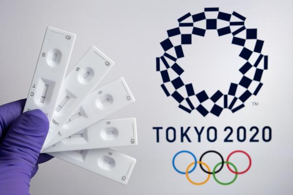 Testes PCR negativos na frente do logotipo das Olimpíadas de Tóquio 2020.