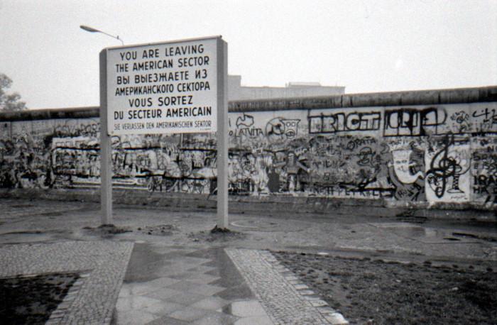 Uma foto do Muro de Berlim, em 1988, e uma placa em várias línguas informando a fronteira da zona americana com a soviética.