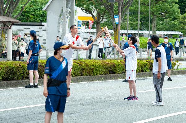 Tocha Olímpica sendo revezada, em público, na cidade de Fuji, em junho de 2021. [5]