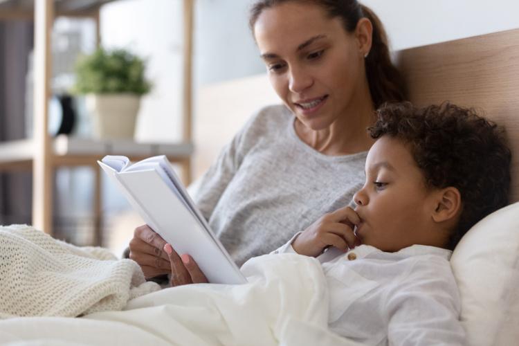 Foto de uma adulta contando história para uma criança.