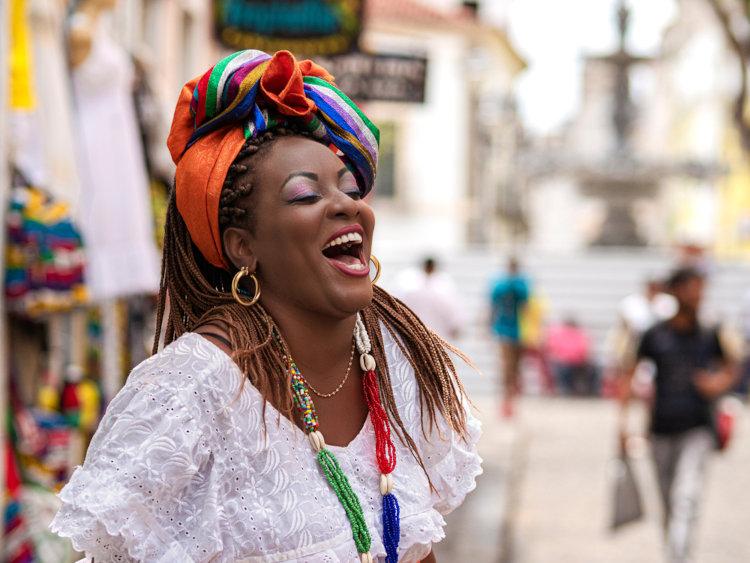 Mulher negra no Centro Histórico de Salvador com trajes típicos de religiões africanas.