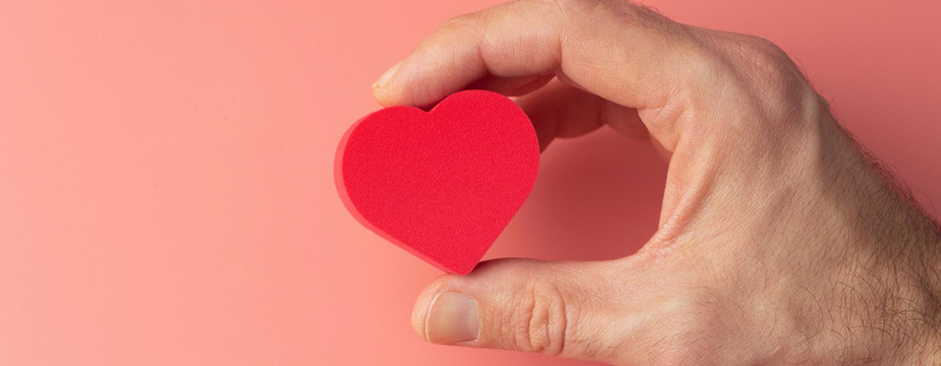 homem segurando coração vermelho