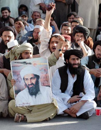 Homens muçulmanos reunidos; um deles segura um cartaz com a imagem de Osama Bin Laden.