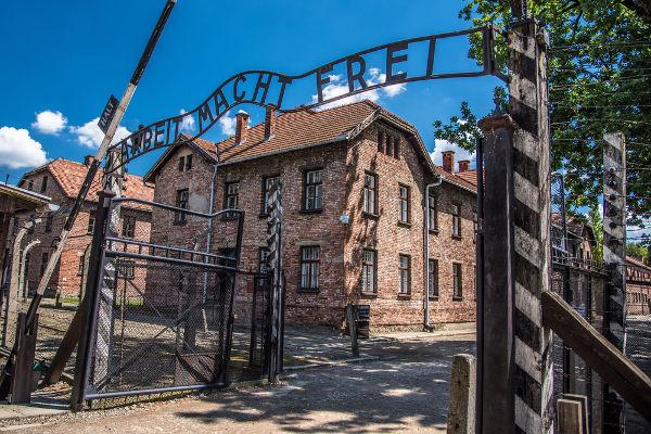 """Portal que fica em uma das entradas de Auschwitz. Nele, está escrito: """"o trabalho liberta""""."""