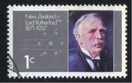 Selo impresso pela Nova Zelândia mostra Rutherford e partículas alfa passando pelo núcleo atômico, por volta de 1971*