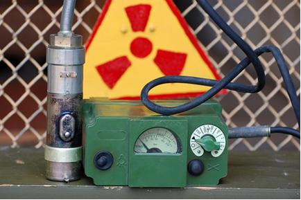 Contador Geiger- Müller e, ao fundo, o símbolo usado para alertar sobre a presença de material radioativo