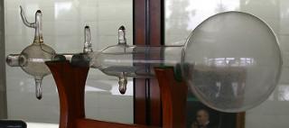 Uma réplica do tubo de Crookes usado por J. J. Thomson em exposição na Universidade de Cambridge *