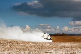 Um caminhão espalhando calcário em pó na terra para melhorar as propriedades do solo, em Lancaster County, Pensilvânia, EUA.