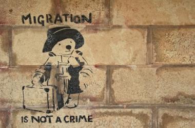 """Pichação em um muro no Reino Unido que afirma que """"migração não é crime"""", em protesto às frequentes posturas xenofóbicas no país. ¹"""